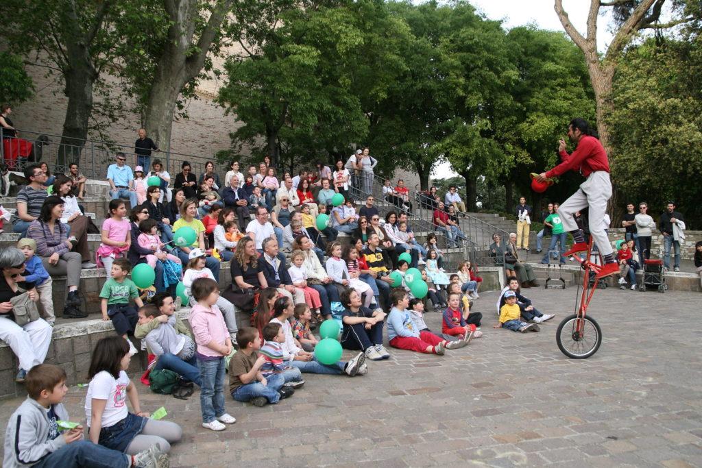 Clown didattico vestito di rosso, davanti al pubblico con la Raffa